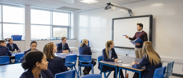 Male teacher is teaching a group of teenagers in a high school lesson.